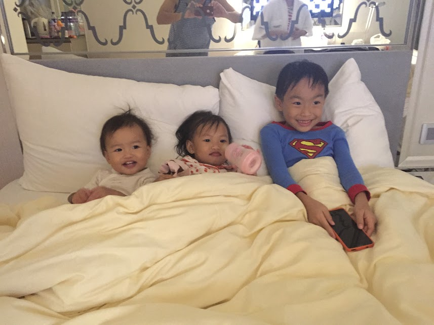 3 kids on the bed in Hotel Cosmopolitan Hong Kong