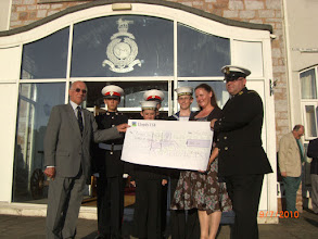 Photo: PRESS RELEASE EXETER FLOTILLA SPONSORS A SEA CADET TO GO TO SEA The Exeter Flotilla has presented a cheque for £300 to the Exmouth Unit Sea Cadet Corps to enable a cadet to go sail training this year. The cheque was presented by the Chairman of the Exeter Flotilla, Captain Ian Brannam RN to the Chairman of the Civilian Committee of the Exmouth Sea Cadets, Mrs Teresa Goodair, and the Officer in Charge of the Unit, CPO Neil Gregory, at a ceremony in the Commando Training Centre Royal Marines Lympstone on Friday 9 July. Captain Brannam said that the Exeter Flotilla often called upon the Exmouth Sea Cadets to provide a colour party at their functions and it was pleasing that they were able to make a small donation to express their thanks for this service. It would enable a cadet to go to sea for a week in T S Royalist, the Sea Cadet sail training ship. CPO Neil Gregory, the OIC of the Unit, said  they would  report back to the Exeter Flotilla on what they had done and where they had been.