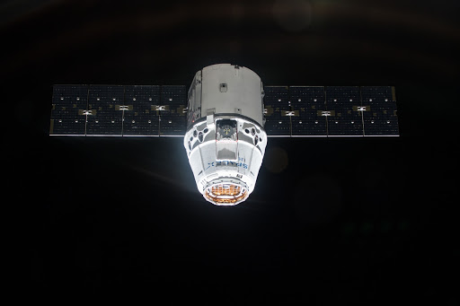 The SpaceX Dragon cargo craft is pictured approaching the International Space Station during an orbital night period.