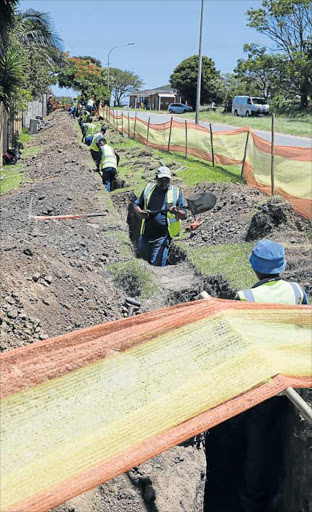 GOOD GROUNDWORK: Workers lay fibre optic infrastructure in trenches down Beacon Bay's Quenera Drive Picture: ALAN EASON