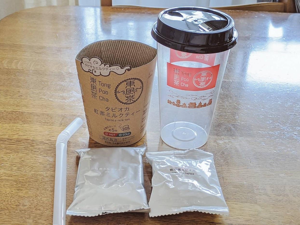 東風茶を開封した画像 手前にタピオカと粉末ミルクティー1袋ずつ、後ろにラベルと空のカップ、ストロー