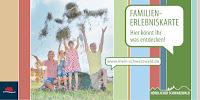 Das Titelbild der Familienerlebniskarte zeigt eine Familie, die vor Freude Heu in die Luft wirft