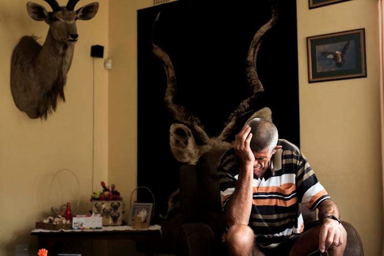 Paul Swart takes a moment in his lounge in Kriel, Mpumalanga, on Wednesday after losing his life's savings through a scam.
