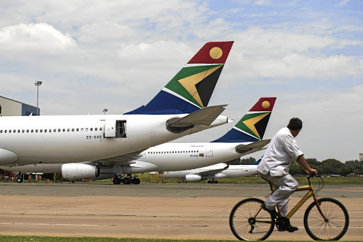 A man cycles past aircraft in the SAA fleet parked at OR Tambo International Airport. Picture: GETTY IMAGES