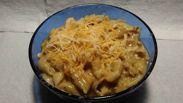 Cobalt Blue Bowl Filled With Cheesy Chicken And Seashell Pasta.