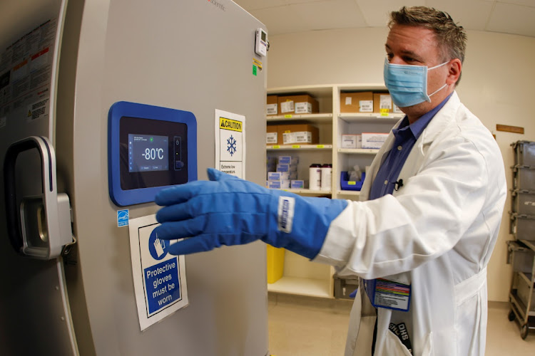 Pharmacy supervisor Kevin Weissman uses a thick glove as he opens the door of a special freezer that will hold the Pfizer vaccine at LAC USC Medical Center in Los Angeles, California. Picture: REUTERS/Mike Blake