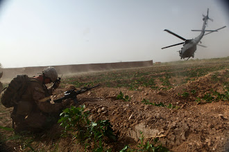 Photo: MARJAH DISTRICT, Helmand province, Afghanistan – A Marine with 2nd Squad, 4th Platoon, Charlie Company, 1st Battalion, 6th Marine Regiment shields himself as a rotary wing aircraft lifts off after performing a medical evacuation during a firefight with insurgents, in the Polpazai village here, Aug. 11. The Marines of Charlie Co., 1/6, engaged insurgents in a firefight while conducting a census patrol in the area.