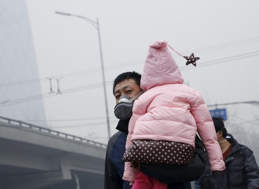 A man wearing a mask carries his baby amid heavy smog after the city issued its first ever 'red alert' for air pollution in Beijing, China. Picture: REUTERS/KIM KYUNG-HOON
