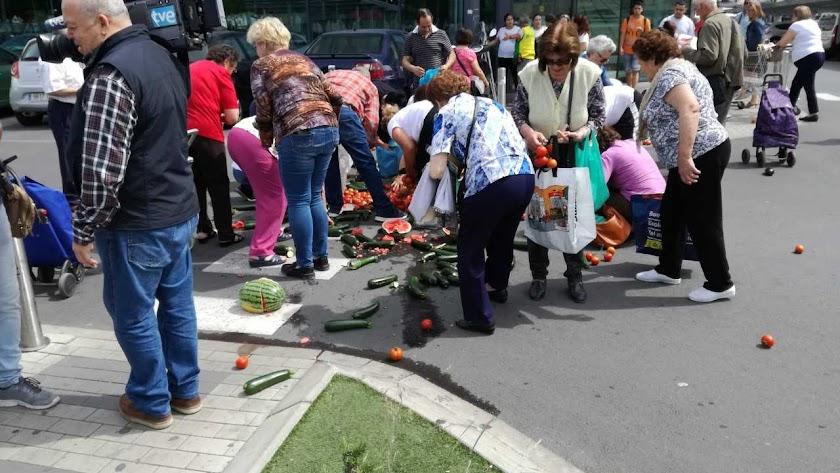 Almerienses cogiendo las verduras arrojadas frente al supermercado.