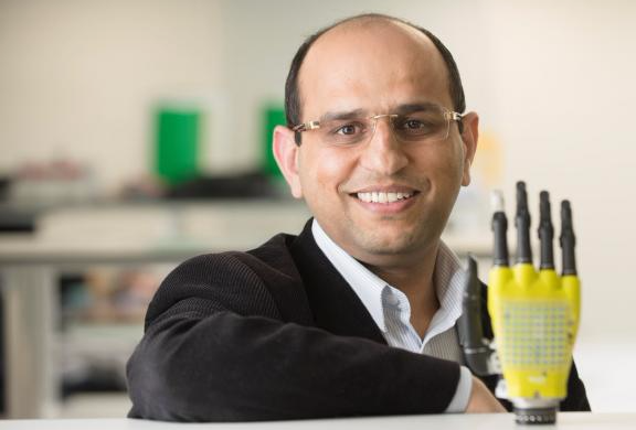Ravinder Dahiya of the University of Glasgow's School of Engineering poses with the prosthetic hand developed by his team at Glasgow University, Scotland. Picture via REUTERS