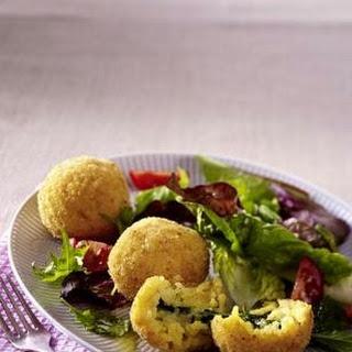 Frittierte gefüllte Reisbällchen (Arancini) zu Blattsalat