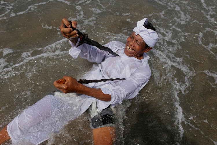 A Balinese Hindu worshiper attempts to stab himself with traditional Kris daggers while in a trance during Melasti, a purification ceremony ahead of the holy day of Nyepi, on a beach in Gianyar, Bali, Indonesia.