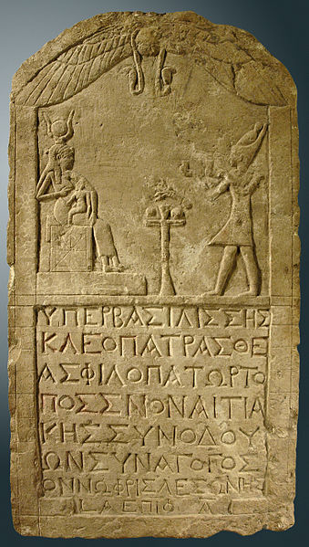 Stone tablet with carving depicting Cleopatra venerating the goddess Isis, with an inscription in Greek at the bottom.