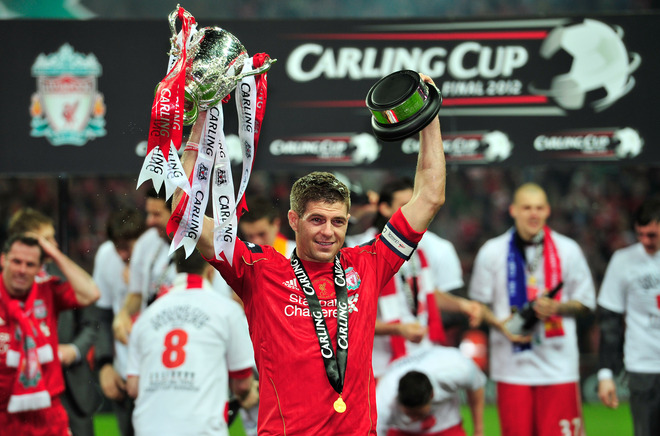 """Photo: Liverpool's English footballer Steven Gerrard celebrates with the trophy after his team beat Cardiff City to win the League Cup Final at Wembley Stadium in London, on February 26, 2012. AFP PHOTO/GLYN KIRK RESTRICTED TO EDITORIAL USE. No use with unauthorized audio, video, data, fixture lists, club/league logos or """"live"""" services. Online in-match use limited to 45 images, no video emulation. No use in betting, games or single club/league/player publications. (Photo credit should read GLYN KIRK/AFP/Getty Images)"""