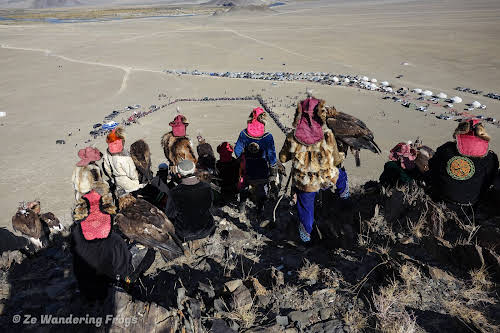 Mongolia. Golden Eagle Festival Olgii. Kazakh Eagle hunters awaiting their turn & view over the rings