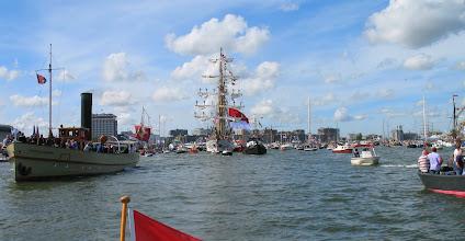 Photo: De Kri Dewaruci (Indonesië) beantwoordt het saluutschot bij het binnenlopen van de IJhaven met een vlagsaluut, terwijl de bemanning staat aangetreden.