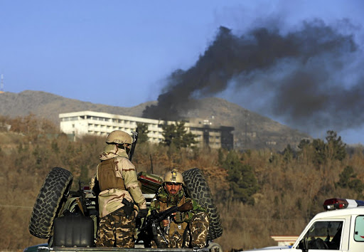 Afghan security forces keep watch as smoke rises from the Intercontinental Hotel in Kabul, on January 21 2018. Picture: REUTERS