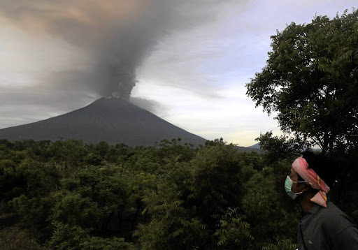 A villager walks in Kubu, Karangasem, as Mount Agung volcano erupts in the background, on Bali, Indonesia, on November 27 2017. Picture: REUTERS