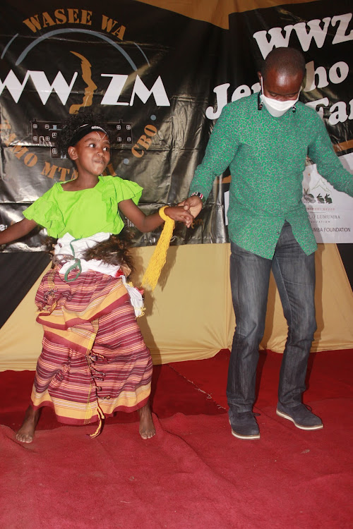 ICT CS Joe Mucheru joins in a dance with a member of a children's dance group at the Jericho Social Hall.