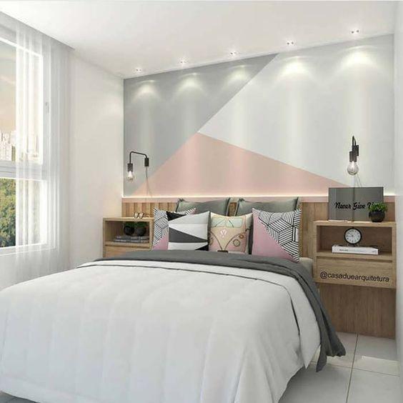 Quarto de casal com cabeceira de madeira e parede da cabeceira com pintura geométrica cinza, rosa e branco.