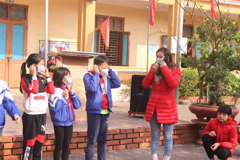Giáo viên hướng dẫn học sinh đeo khẩu trang đúng cách để đảm bảo an toàn, phòng, chống dịch bệnh do chủng virus Corona mới gây ra