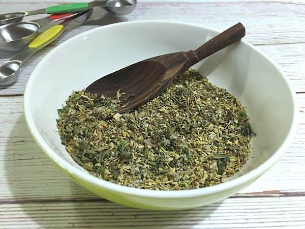 A Mix Of Herbs In A Small Bowl.