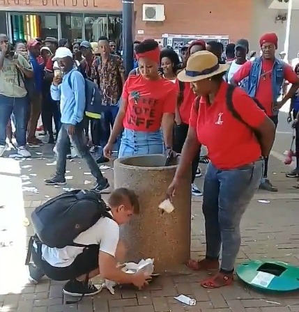 University of the Free State (UFS) student Eckhard Binding seems unfazed as he tries to dispose of rubbish, only for two women in EFF T-shirts to throw it out.