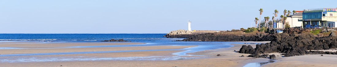 Photo: A panoramic view of the beach and the shore, the lighthouse and the town.