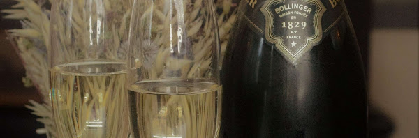 a bottle of champagne with two full glasses of champagne