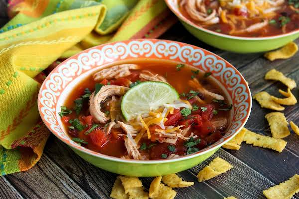 A Bowl Of Easy Chicken Taco Soup With A Lime Wedge.
