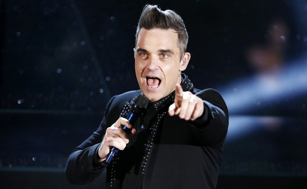 Robbie Williams pointing whilst performing at one of his shows