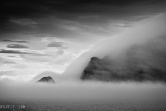 Photo: Coburg island incognito Coburg island, Canadian Arctic from the blog http://www.kylefoto.com  The arctic can be one of the most desolate environments. The landscapes have a way of amplifying loneliness and introspection while still keeping you in awe of the harsh reality of this cold northern desert.  The cool arctic doesn't hold much moisture, therefore it doesn't snow very often, giving many places in the north the same amount of precipitation of the sahara desert. So when the fog rolls in I was sure to relish this sight as this dramatic island is shrouded in a blanked of mist.  These cliffs are homes to many species of birds who depend on the steepness and hostility of these cliffs to protect their eggs from land dwelling predators. Many birds lay pear shaped eggs ensuring that if an egg was to roll, it would roll back into the nest instead of the cliff. Being one of the most important sites in the arctic it's home to over 220,000 pairs of nesting birds.  Photographic Details: Taken in the early morning it was somewhat dim out, I had to use a relatively low shutterspeed of 1/160th of a second, handheld from a ship that was bobbing in the ocean, where a tripod wouldn't be much of an aid. Canon 5D 1/160s f/7.1 ISO100 100mm  #moodymonday