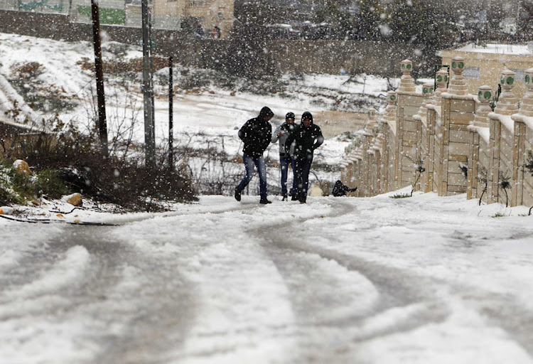 COLD SNAP: Palestinians walk along a snow-covered road in the West Bank village of Halhul near Hebron. Picture: REUTERS