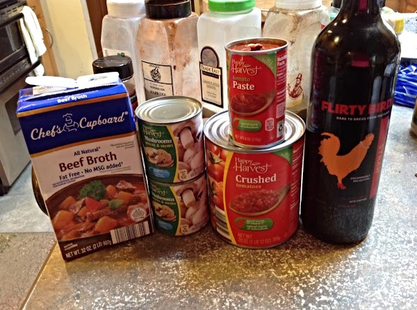 Now add in the beef broth, mushrooms, crushed tomatoes, tomato paste and red wine,...