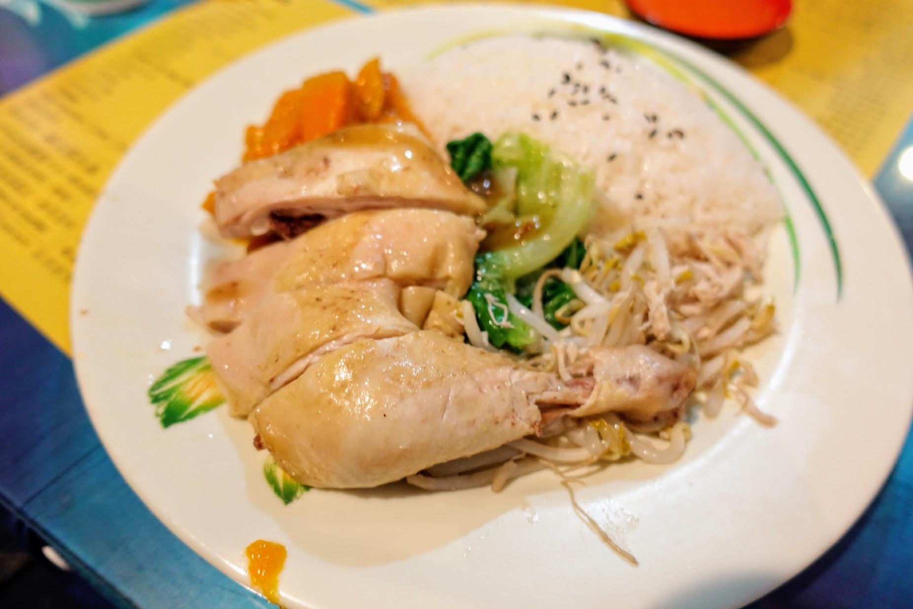 海南雞飯,旁邊有三樣配菜和主力的雞腿,另外也有醬汁可以沾