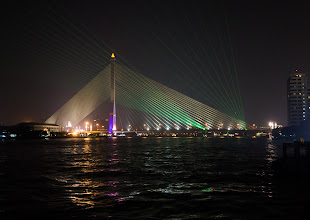 """Photo: The Rama VIII cable-stayed bridge across the river, with extra """"webbing"""" provided at night by green lasers."""