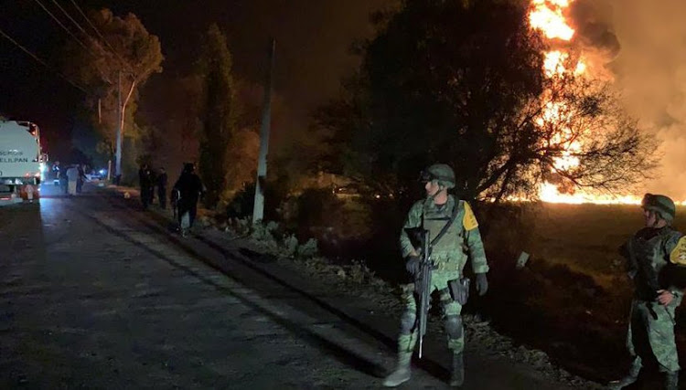 Military personnel watch as flames engulf an area after a ruptured fuel pipeline exploded, in the municipality of Tlahuelilpan, Hidalgo, Mexico, near the Tula refinery of state oil firm Petroleos Mexicanos (Pemex), January 18, 2019