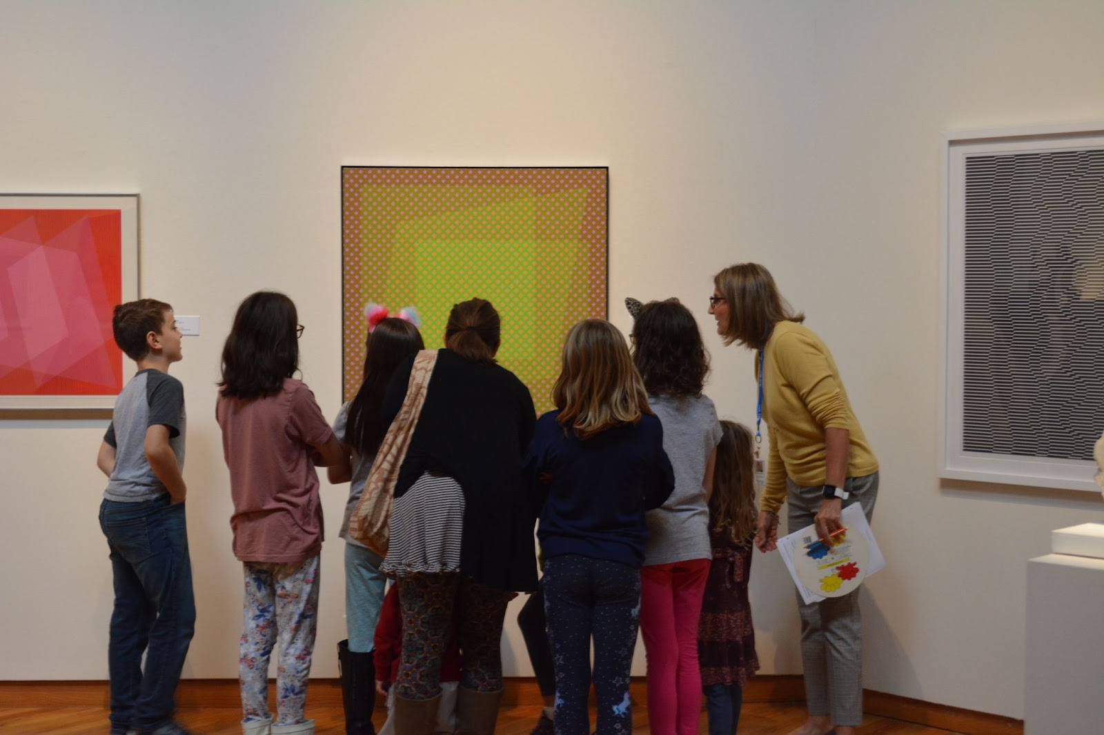 Docent Barb Young-Miller gets up close to a Julian Stanczak painting with a group of school students on a tour.