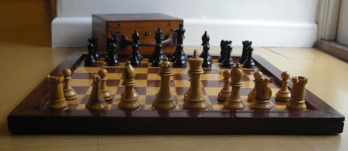 Photo: C346 - British Chess Company 'Popular' set c.1899-1902; No 2 size   Boxwood / ebonised boxwood, nicely polished and heavily weighted in a lovely large box  K = 3.93in / 100mm Q's with 10(W)/11(B) points to the coronet (my smaller Pop has 9) R's with 5 crennelations - typical of Pops B's with full balls and deep gashes to the mitres (down to the collar), again, typical of these sets  Not as 'refined' or distinctive as BCC's main-line sets, these are excellent playing sets in their own right, with 'chunky' pieces that sit well on the board (my larger BCC board CH98, in the above image). They formed BCC's cheaper range in the dying days of the firm's production period,  but, as BCC-crown-stamped sets, are not seen very frequently. They were most likely bought in - Ayres being a possible source.  There is damage to: one white rook's castelations, two pawn's collars and a slight crack to the base of the black queen - but I find I  become more tolerant of such as time goes by,  and I can live with it happily.