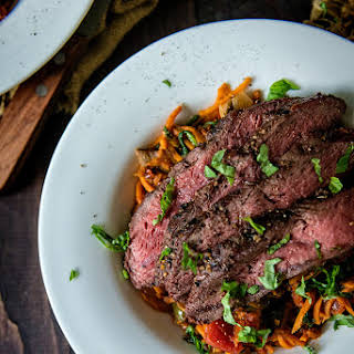 Whole 30 Grilled Flat Iron Steak Over Marinara Tossed Sweet Potato Noodles.