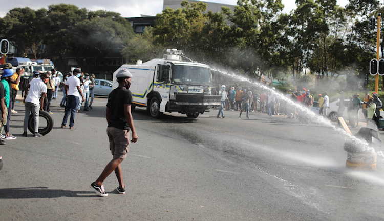 A water cannon puts out burning barricades, 15 March 2021, in Braamfontein, Johannesburg during a national student protest against the exclusion of students with historical debt and free decolonised education.