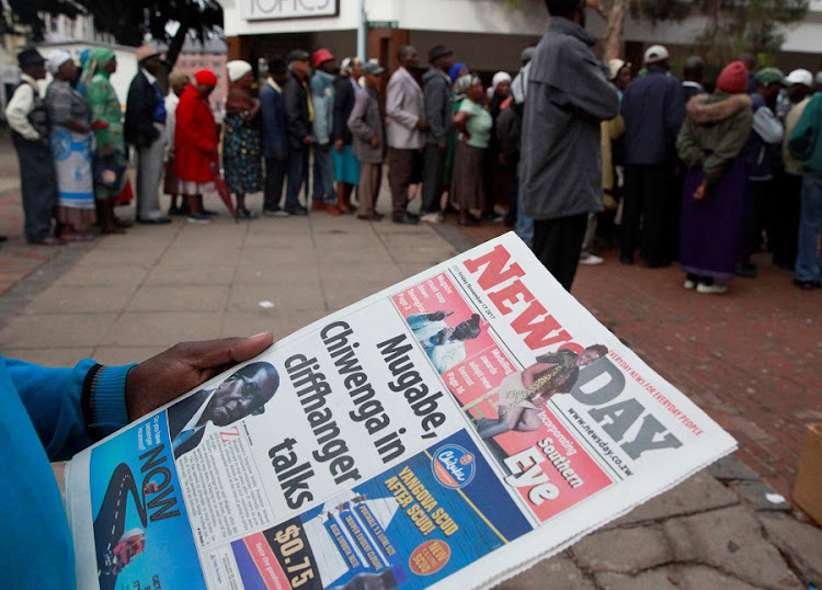 A man reads a newspaper as residents queue to draw money at a bank in Harare, Zimbabwe. Picture: REUTERS/PHILIMON BULAWAYO