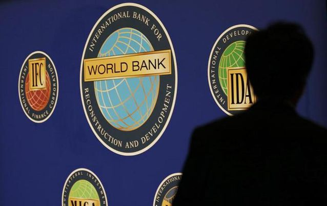 A man is silhouetted against the logo of the World Bank. Picture: REUTERS