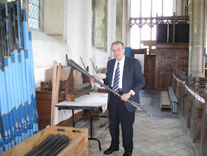 Photo: The organist at Swanton Morley Church explains planned renovations to its ancient pipe organ.