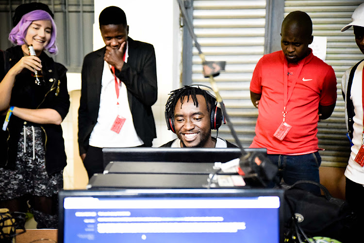 A MAZE attendees at the Tshimologong Precinct watch and play one of the featured games at the festival last year.