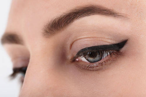 close-up of a woman's eyes with heavy black winged tattoo eyeliner