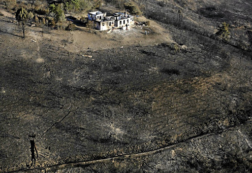 Bleak view:  Scorched land surrounds homes lost to fires in Knysna. Extreme weather events are among the predictions of scientists studying climate change.Picture: ESA ALEXANDER