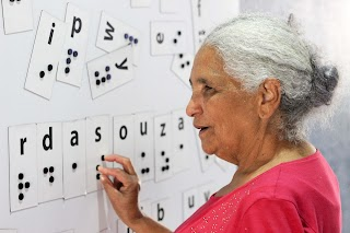 Uma mulher com deficiência visual lendo Braille em uma lousa.