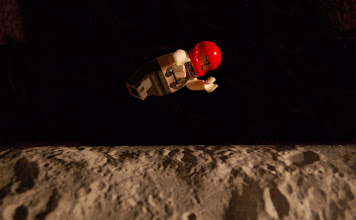 Photo: Requirement 4 (levitation): The Lego astronaut man floats and flies above the moon! This photograph is created through a stack of 2 photos and highly manipulated in Photoshop. I like the one source of light (coming from... the sun!), provided by a desk lamp, and the whole set of objects is placed against a black fleece jacket. The moon surface is created by draping a print-out of the moon surface, carefully balanced on a medicine ball for the curved (though 1D) effect.