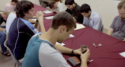 Photo: Students gather together for prayer before going over end-of-year business with their professors.